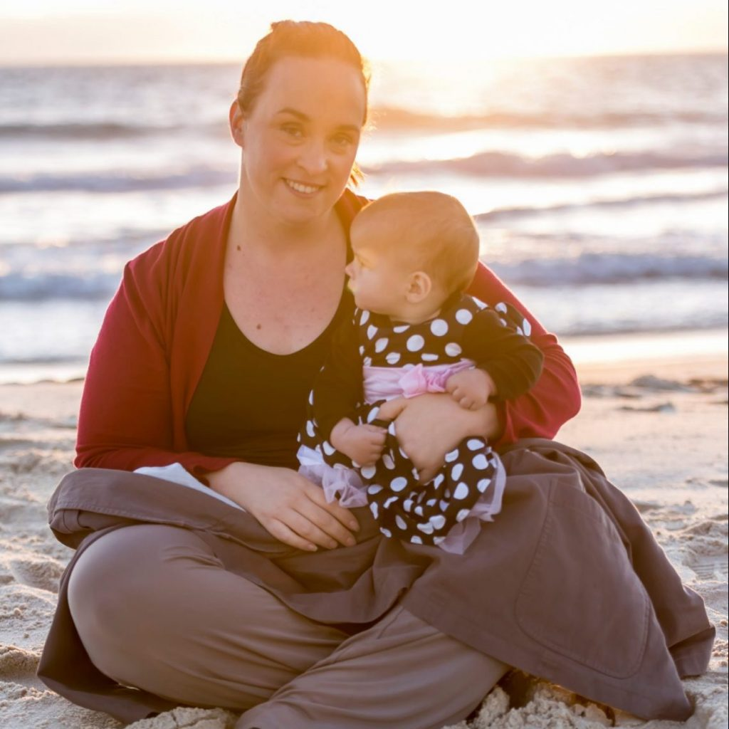 women on beach at sunset holding a baby