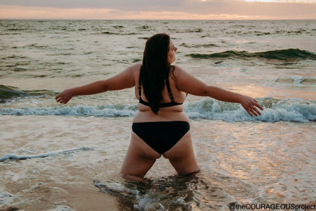 Voluptuous woman kneeling in shallow water, back to us with black bikini and long brown hair.  Arms stretched out to the sides like she is going to hug someone, sun reflecting off the water.