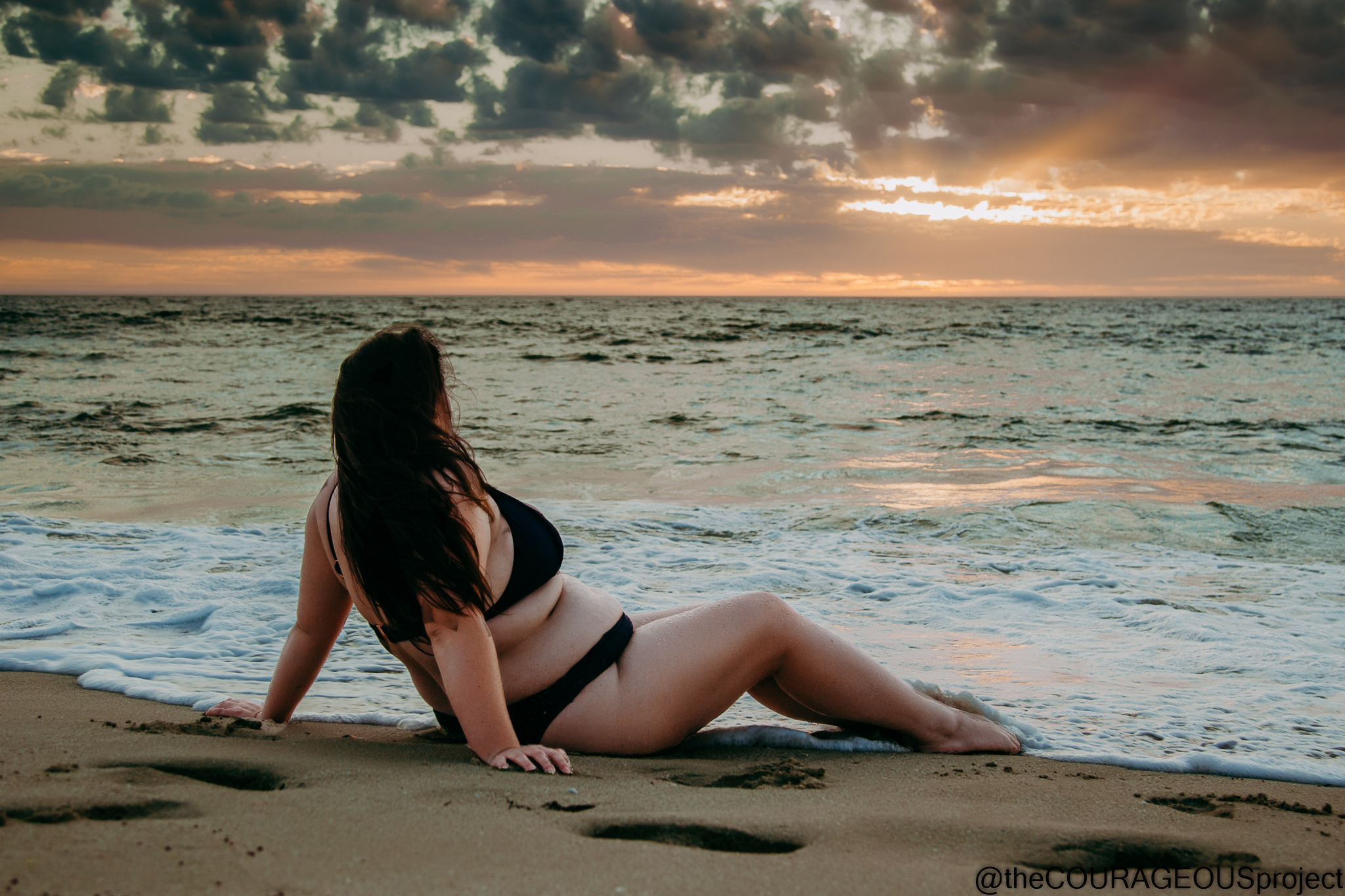 Plump young woman sitting on waters edge at beach at sunset, looking at clouds in the sky with sun shining through.  Woman is wearing a black bikini, leaning back on her hands and her long dark brown hair is flowing down her back and arms.