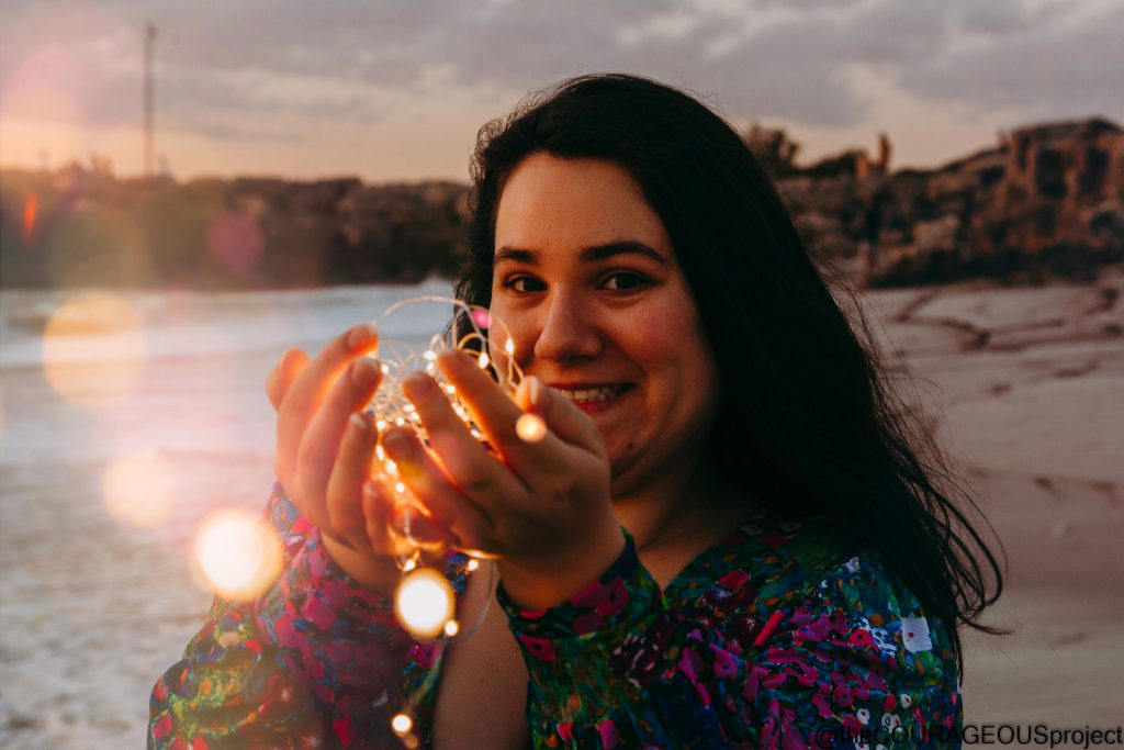 Young woman in floral dress with green and blue colours with small pink, red and white flowers, looking at the camera side on with her hands up to her face holding a ball of fairy lights, a string of lights coming towards the camera.