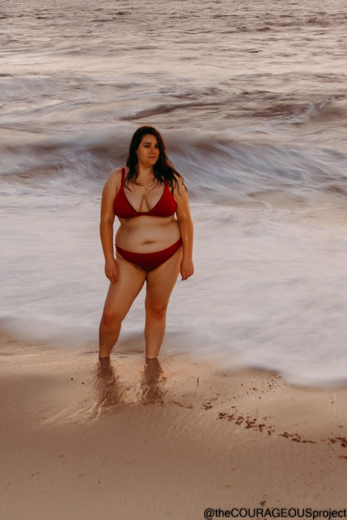 Young voluptuous woman in red bikini, standing in shallow beach water that has a white hazy motion to it.