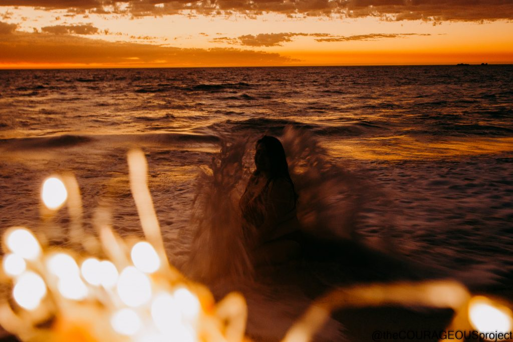 A silhouette of someone getting completely covered in water by the waves, water caught in motion as it comes up, fairy lights up closer to camera.