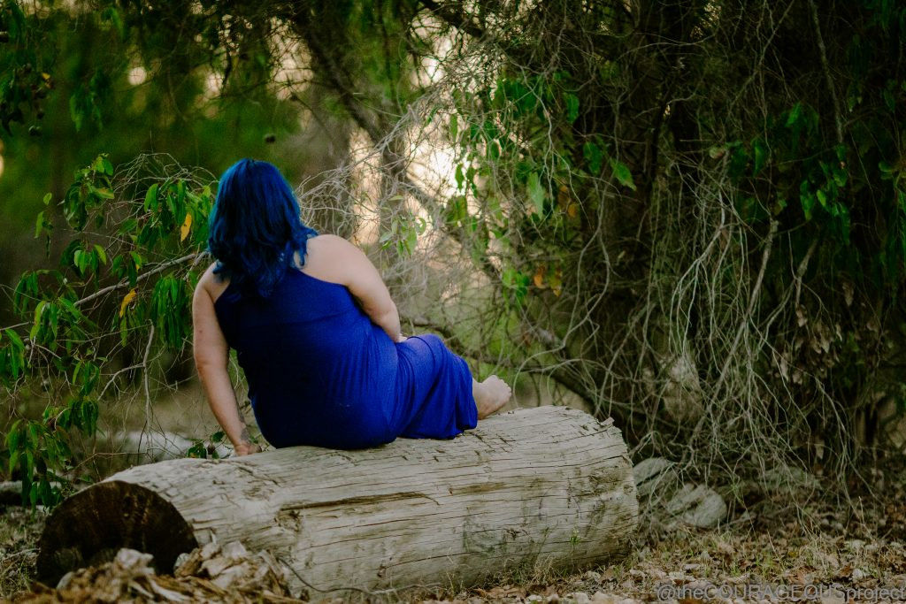 A woman sitting on a long log, legs out.  Blue dress and blue hair, looking off into the distance.